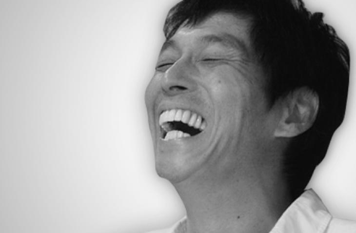 歯を出して笑っているモノクロの明石家さんまの画像・壁紙